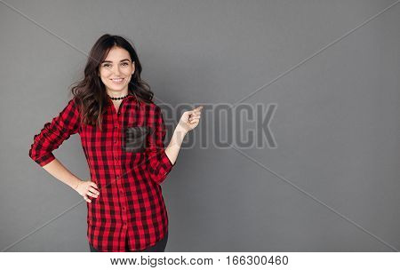 Pretty cheerful woman gesturing with finger and showing away to a copy space on grey background. Student Girl in casual shirt pointing to blank space