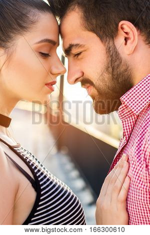 Couple is touching foreheads. Woman's hand on man's chest. Nothing can break us apart.