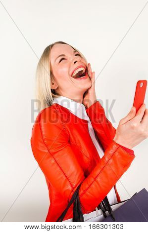 Portrait of young smiling woman in a red jacket with shopping bags on a white background. Woman with shopping bags talking on the phone.
