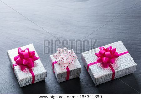 Love and still life concept. Valentines day holiday gift boxes on a grunge black table. Copy space background