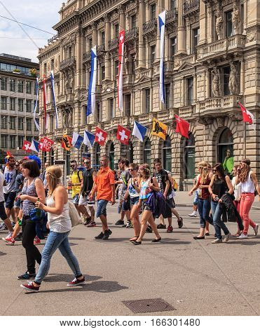 Zurich, Switzerland - 2 August, 2014: people on Paradeplatz square on the day of Street Parade, headquarter of the Credit Suisse building, decorated with flags of Zurich and Switzerland. Street Parade is the most attended technoparade in Europe.