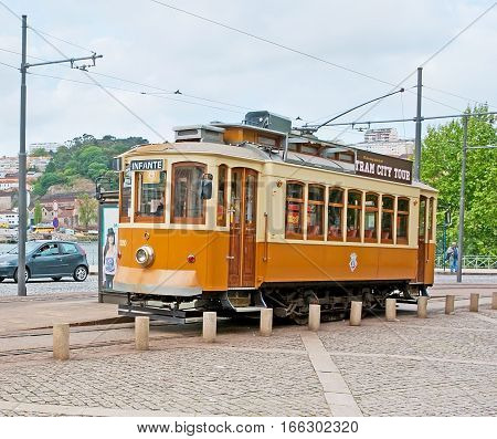 PORTO PORTUGAL - APRIL 30 2012: The vintage tram waits for the tourists at the station with the Douro River embankment on the background on April 30 in Porto.