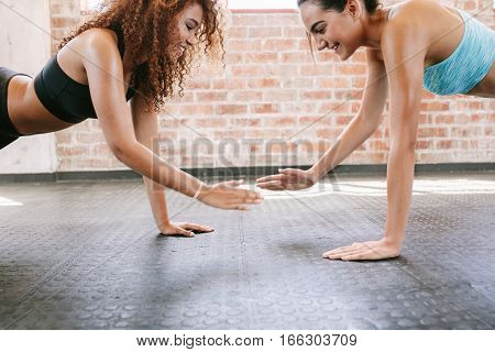 Side view shot of two young female exercising together in gym. Women doing pushups together.