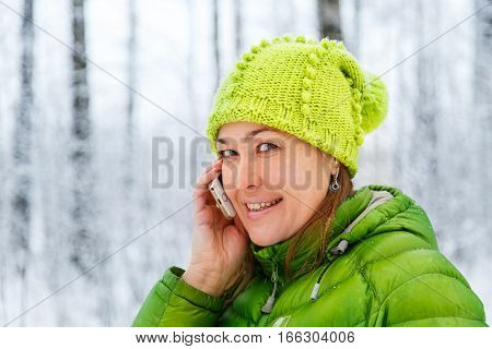 Beautiful girl talking on the phone in the winter forest.
