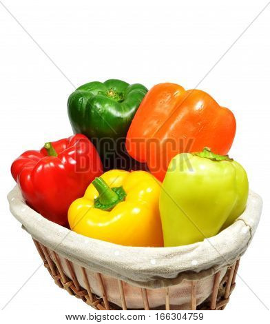Five multi-colored sweet bell peppers in wicker basket. Isolated on white background. Closeup