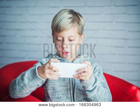 Cute blond boy playing with a smartphone