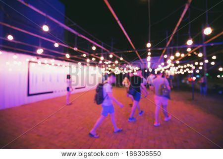 Blurry scene of people on night walkway in purple theme. Walkway decorated by bright light lamp on ceiling and white wall on the left.