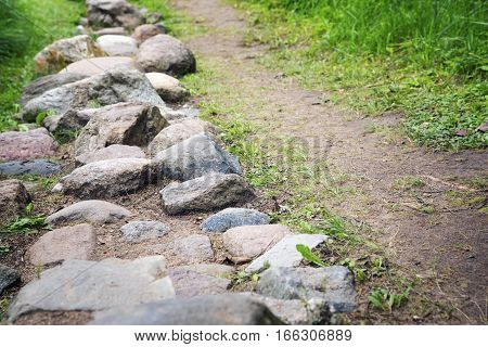 Way from cobble-stones on green herbs a background
