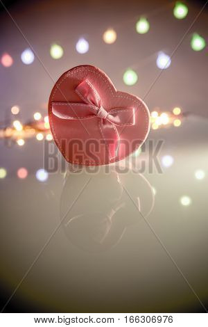 gift box in the form of heart on the background illumination
