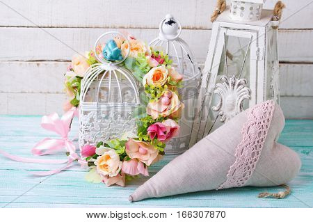 Wedding inspiration.Decorative heart flower wreath and lanterns with candles on wooden background. Selective focus.