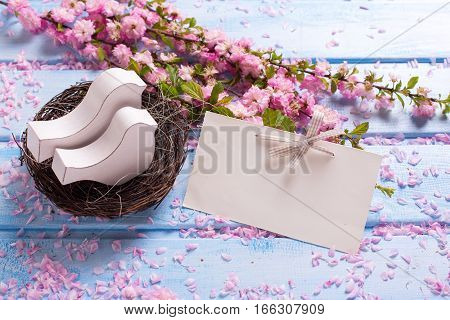Pink sakura flowers empty tag and two white wooden decorative birds in nest on blue wooden planks. Selective focus. Place for text.