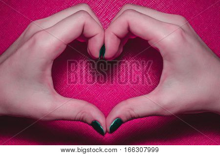 Women palms in the shape of a heart on a pink background tekstured. Symbol of love Valentine Day, fourteen february.