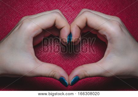 Women palms in the shape of a heart on a red background tekstured. Symbol of love Valentine Day, fourteen february.