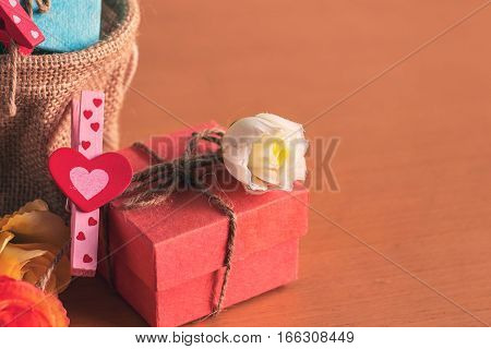 Heart and gift box on a wooden table.