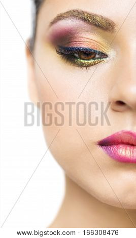 Close up portrait of a beautiful young brunette model with bright make up. Close up of abstract multicolor make up. Makeup Pigment powder explosion
