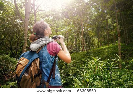 Woman hiker watching through binoculars wild birds in the rainforest. Bird watching tours. Ecotourism concept image travel.