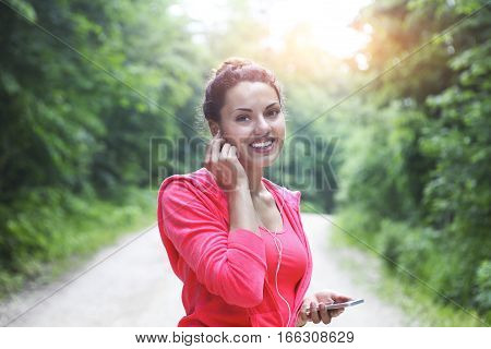 Brunette young woman jogging and listening to music outdoors.