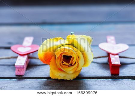 rose and heart on a wooden table.