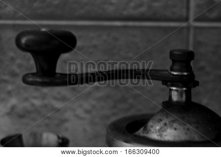 Vintage side view of retro coffee, pepper or sugar grinder or mill with mechanical rustic handle close up in black and white style
