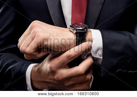 Partial view of businessman in black suit checking wristwatch
