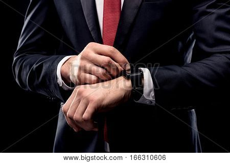 Partial view of businessman in black suit checking smartwatch