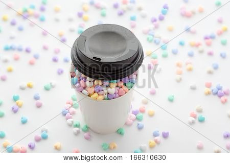 Cup of Love focus on small colorful pastel heart beads in paper cup with cover and some small heart beads in the blurred background.