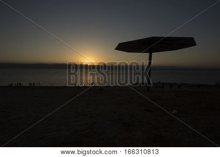 Tent, stand, canopy in Dead sea beach at sunset