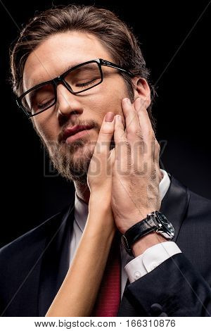 Close-up portrait of handsome businessman in eyeglasses with female hand on face