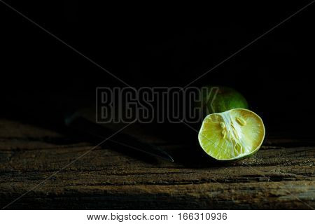 Lemon and side of lemon and knife on wood plate with moody and dark style and background