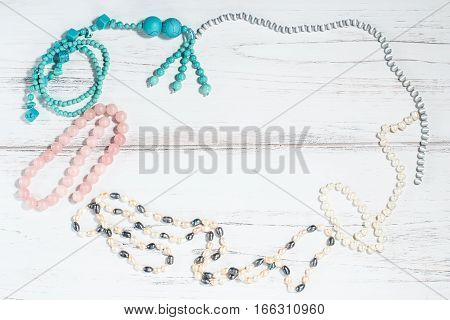 Frame of pearl necklace and turquoise beads on a wooden background with copyspace