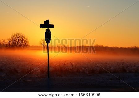 Country Crossroads Sunrise. Rural intersection in heavy fog on a wintry morning with a stop sign silhouette. Jeddo, Michigan.