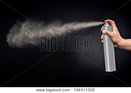 Close-up view of human hand and spray bottle on black