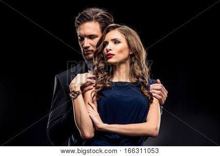 Portrait of beautiful sensual couple in elegant clothes posing on black