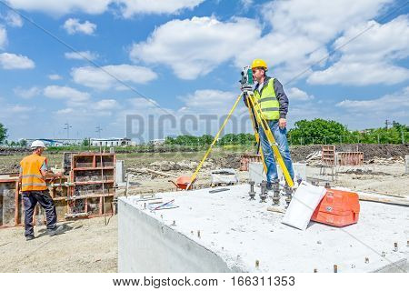 Zrenjanin Vojvodina Serbia - May 25 2015: Surveyor engineer is measuring level on construction site. Surveyors ensure precise measurements before undertaking large construction projects.