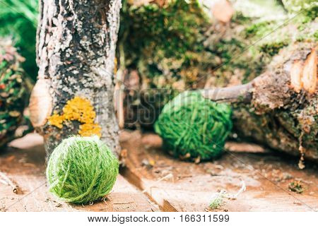 Green yarn clews amid natural raw mossed logs. Closeup view. Concept of eco friendly knitting shop