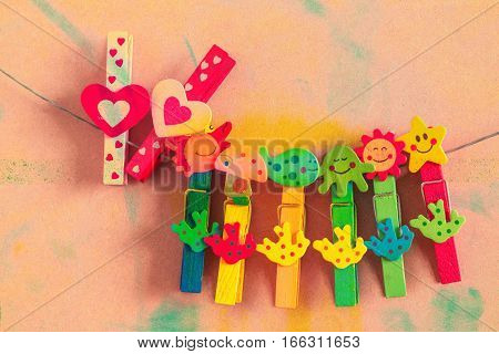 Clothespin colorful hearts on the old wood.