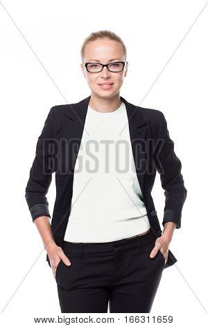 Portrait of beautiful smart young businesswoman in business attire wearin black eyeglasses, standing with arms in pockets against white background.