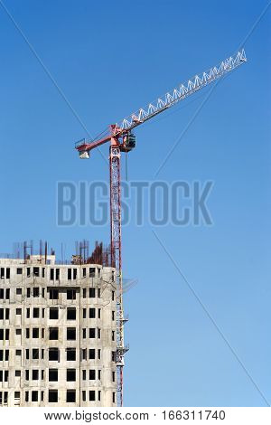 Hoisting tower crane in construction process of residential building over clear blue sky. Vertical photo