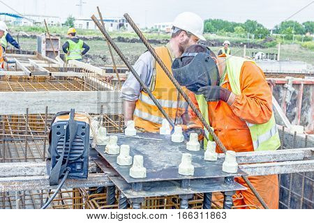 Zrenjanin Vojvodina Serbia - May 29 2015: Industrial shot of construction workers who are welding metal frame cage of armature inside of demountable wooden mold for concreting pillar base.