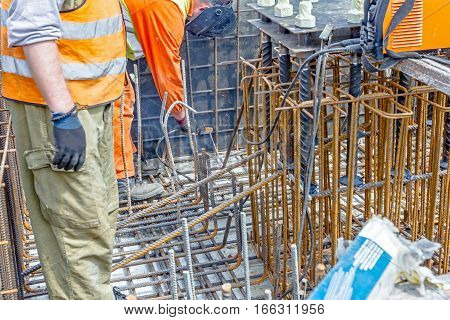 Industrial shot of construction workers who are welding metal frame cage of armature inside of demountable wooden mold for concreting pillar base.