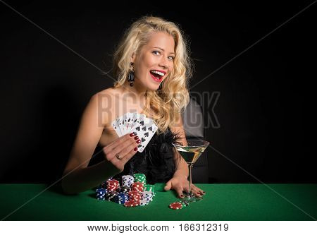 Excited and happy woman playing poker at casino