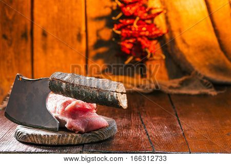 Piece of pork loin on the rustic cutting board. Meat chopper. Fire lighted background with chili