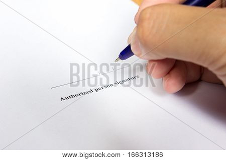 Business man hold the pen for sign in authorization signature space background