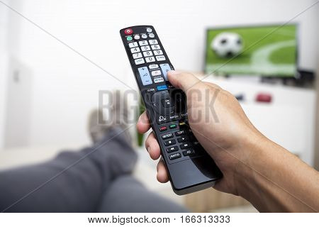 Watching TV. Remote control in hand. Watching football on TV. Man lying on the couch watching TV