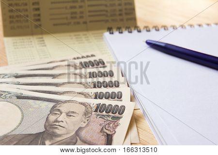 Saving account passbook japanese yen note book and pen