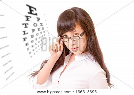 Asian Woman Peering Over Top Of Spectacles Next To Eyechart