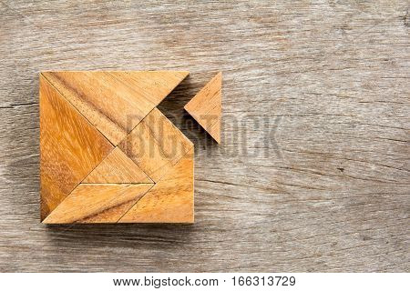 Tangram puzzle with one piece is wait to match the square shape on wood background (Concept for love fulfillment)