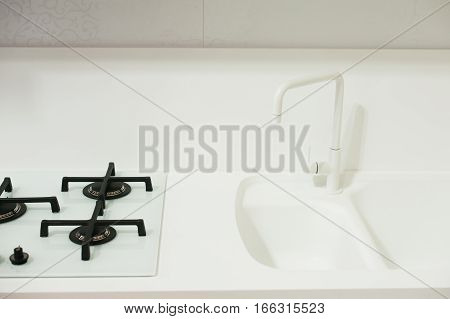 Angle view of kitchen sink with silver faucet