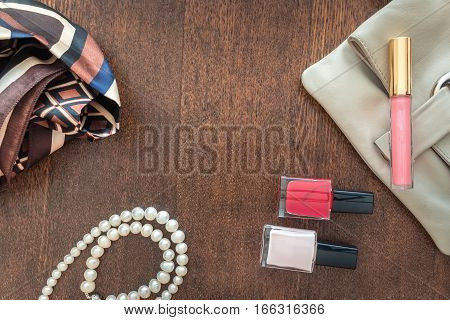 Cosmetics and women's accessories on wooden background. Clutch, pearl, shawl and red nail polish