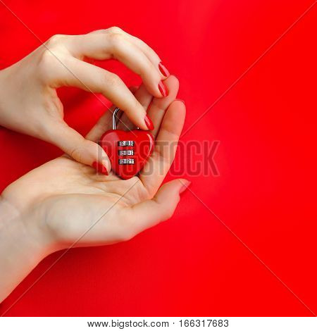 Padlock Heart-shape In Women's Hands On Red Background